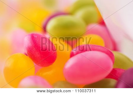 Jelly beans or sugar coated gummy candy inside a plastic bag. Extremely shallow depth of field.