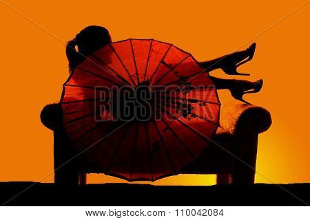 Silhouette Of Woman On Couch Behind Umbrella