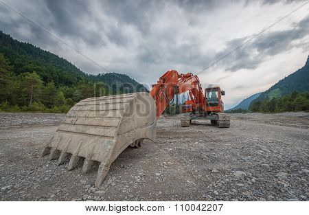 heavy red digger with huge shovel in gravel