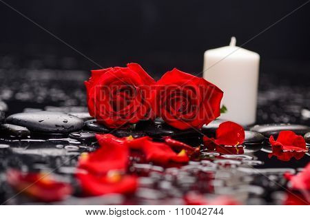 Two red rose, petals with red candle and therapy stones