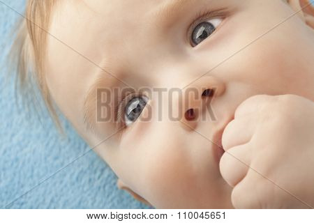 Portrait of a baby sucking a finger close up