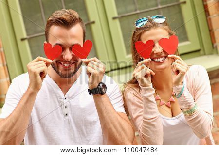 A picture of a young romantic couple covering eyes with hearts in the city