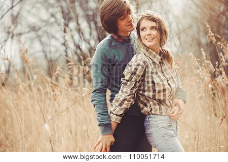 young happy loving couple walking on country field, cozy mood, rural scene