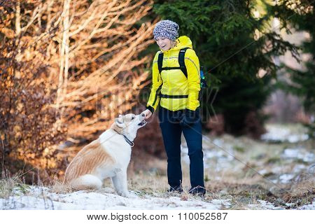 Happy Woman Walking In Winter Forest With Dog