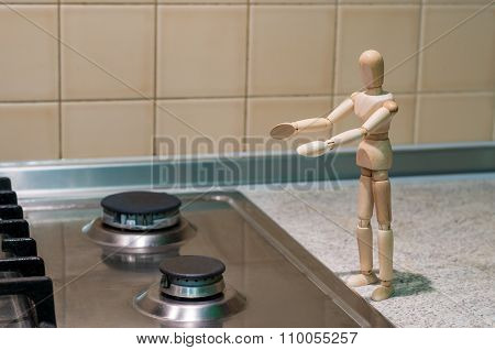 Wooden dummy, mannequin or man figurine, silhouette stand near a gas burner outstretched hands. Gas