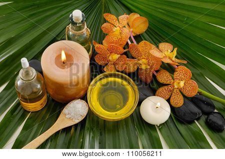 Branch orchid ,spa oil ,towel, salt in bowl ,candle on palm leaf