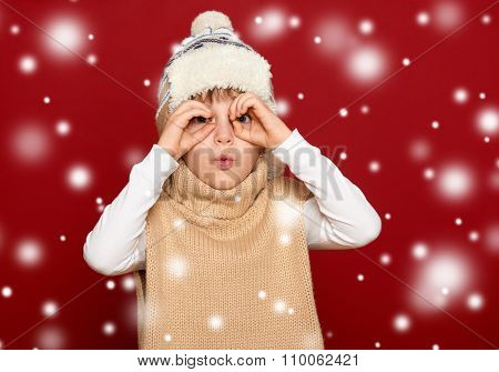 winter people concept - girl in hat and sweater on red background look through binoculars