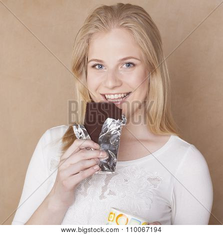 young cute blond girl eating chocolate and drinking coffee close up
