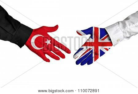 Turkey and United Kingdom leaders shaking hands on a deal agreement