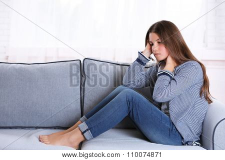 Young upset girl sitting on the sofa in her room