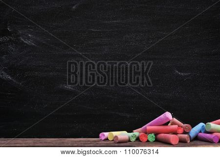 Multicoloured chalk on blackboard background