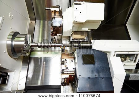 metalworking  industry. cutting tool processing steel metal shaft on lathe machine in workshop