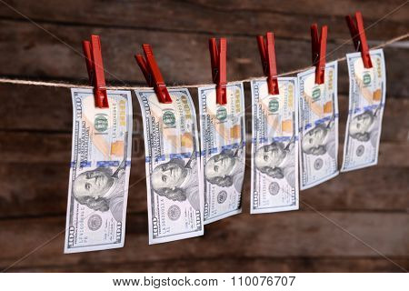 Concept of money laundering - dollars are drying on cord on wooden background