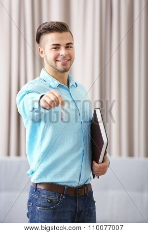 Friendly male estate-agent with key on light background