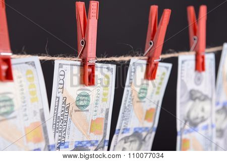 Concept of money laundering - dollars are drying on red clips on cord on black background
