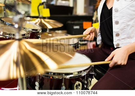 music, sale, people, musical instruments and entertainment concept - close up of female musician playing cymbals at music store