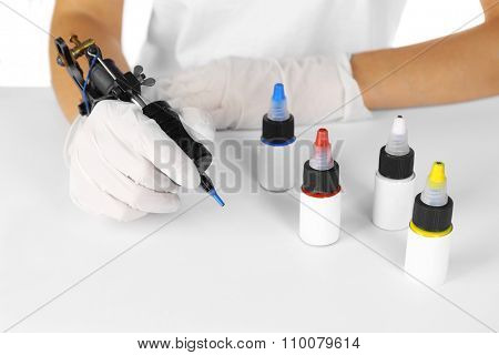 Tattoo machine in hand and colourful ink on white background