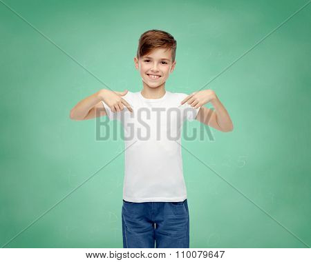 school, education, childhood, advertisement and people concept - happy boy in white t-shirt and jeans pointing finger to himself over green chalk board background