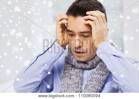 healthcare, flu, people and medicine concept - close up of ill man with flu suffering from headache at home over snow effect