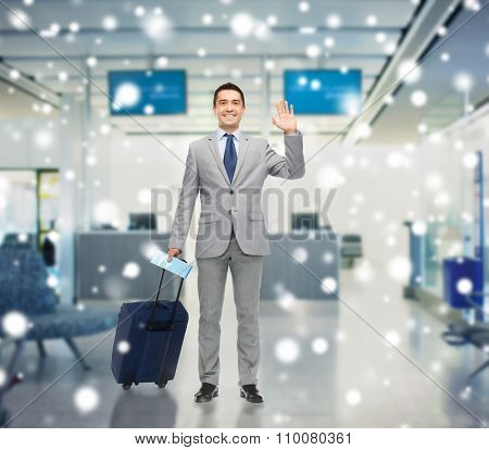 business trip, traveling, luggage and people concept - happy businessman in suit with travel bag and air ticket waving hand over airport background and snow effect