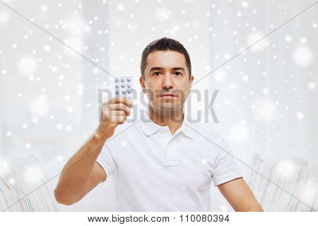 people, medication, medicine and health care concept - man showing pack of pills at home over snow effect