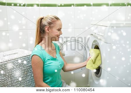 people, housework, laundry and housekeeping concept - happy woman putting laundry into washing machine at home over snow effect