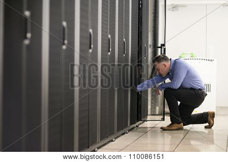 Technician walking in server hallway at the data centre
