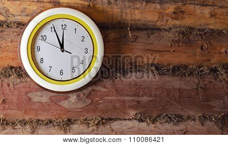 The Clock On The Old Wall Made Of Logs