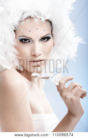 Luxurious winter beauty holding crystal gem, wearing professional makeup with rhinestones.