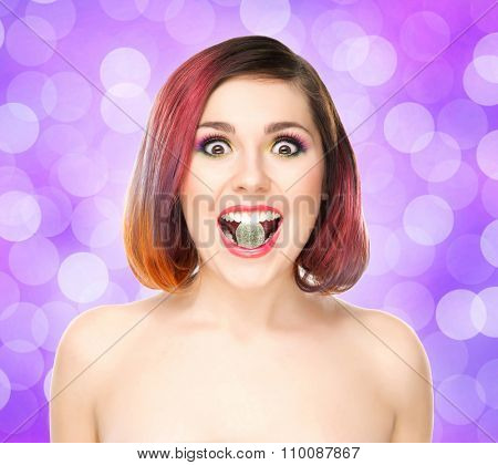 Beautiful girl with colored hair having a jelly in mouth on bubbly background.