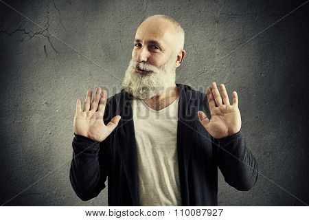 senior bearded man showing refusal sign and looking at camera over dark background