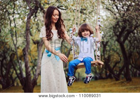 Happy dressy mother and toddler son on swing in spring garden celebrating birthday outdoor