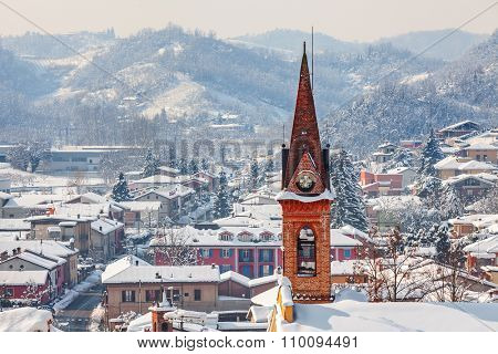 Church bell tower and small town covered with snow in Piedmont, Northern Italy.