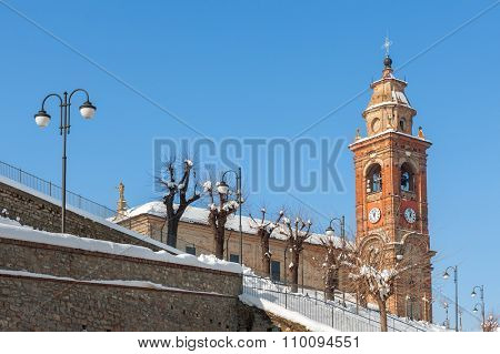 Street lamppost and parish church covered with snow under blue sky in Piedmont, Northern Italy.