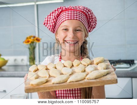smiling little girl with raw patties on a board
