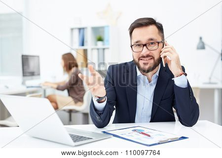Handsome employer speaking on cellphone and looking at camera