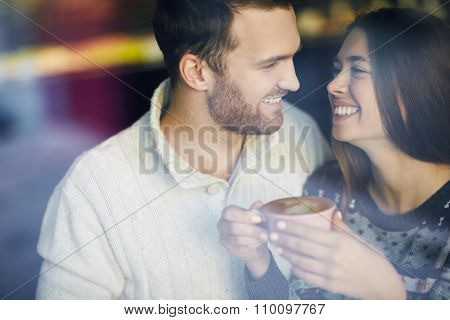 Amorous dates looking at one another while having coffee