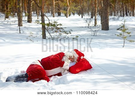 Tired Santa Claus sleeping in snowdrift