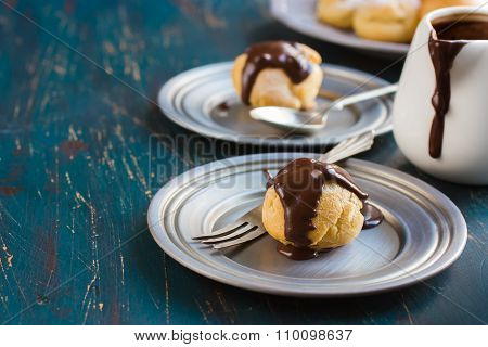Profiteroles With Cream And Chocolate Sauce On Dark Blue Background