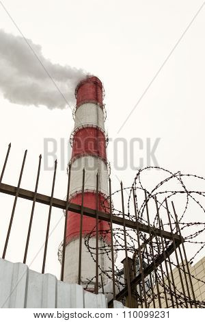 Red And White Industrial Chimney And Barbed Wire