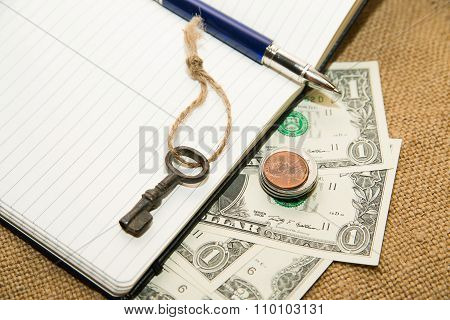 Opened Notebook, Pen And Money On The Old Tissue