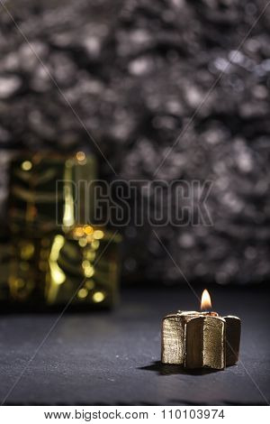 Lit Golden Candle With Christmas Decoration And Gift Background