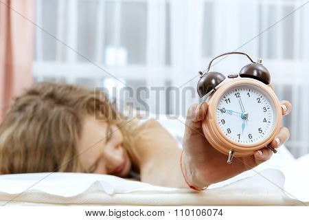 Woman with alarmclock on the bed.
