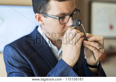 Jeweler Examining Diamond Through Loupe