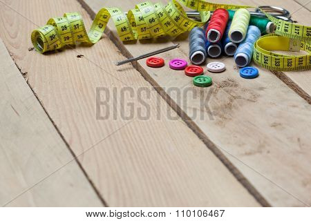 Buttons, Threads And Tape For Needlework On Wood Background