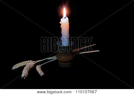 Candle And Three Ears On A Dark Background
