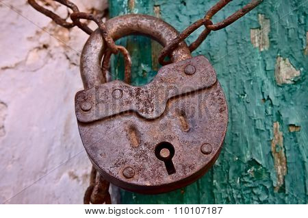On The Old Wooden Door, Installed A Rusty Padlock
