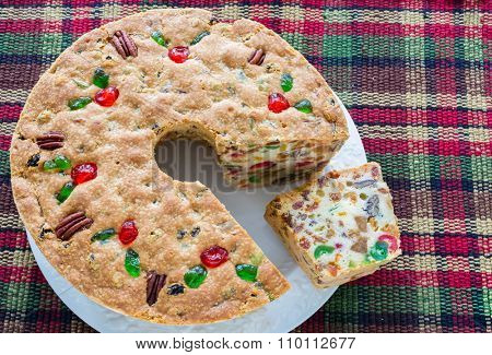 A homemade light Christmas fruitcake on a plaid tablecloth.