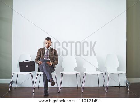 Businessman with touchpad sitting on chair and waiting
