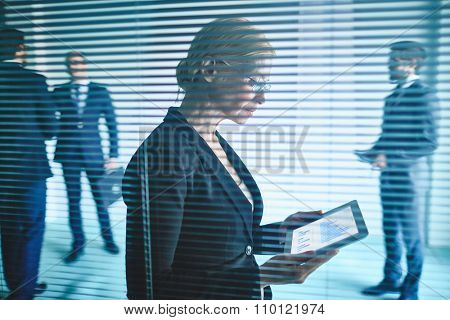 Businesswoman looking at touchpad with graphs behind jalousie at office